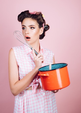 pretty girl in vintage style. pin up woman with trendy makeup. pinup girl with fashion hair. perfect housewife. retro woman cooking in kitchen. Cooking with passion Stock Photo