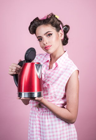 pretty girl in vintage style. pinup girl with fashion hair. perfect housewife. pin up woman with trendy makeup. retro woman cooking in kitchen. Morning routine Stock Photo