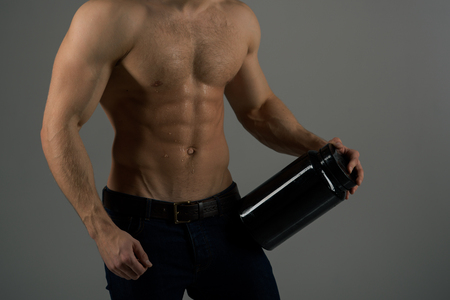 On a diet. Man with six pack abs. Stimulating muscle growth with anabolic steroids. Anabolic hormone increases muscle strength. Vitamin nutrition. Healthy diet. Strong man hold vitamin bottles