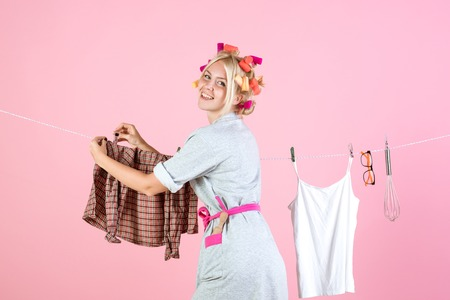 stressed retro housewife. Maid or housewife cares about house. Vintage housekeeper woman. Busy mother. Multitasking mom. Performing Different Household Duties. Every day chores Stock Photo
