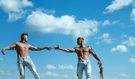 Primed for victory. Men shows off their strength against competitors. Athletic twins on opposite sides. Twins competitors with muscular bodies. Strong men pull rope with muscular hand strength