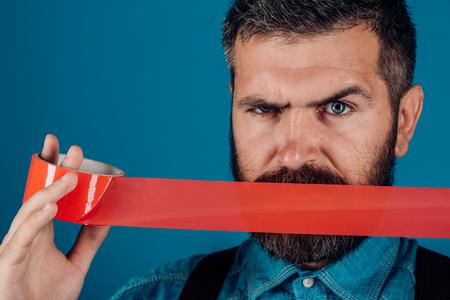 Giornata internazionale dei diritti umani. censura. Brutale maschio barbuto. uomo che avvolge la bocca con del nastro adesivo. Controllo mentale e propaganda. Concetto di libertà di parola e di stampa. aggressione nascosta.