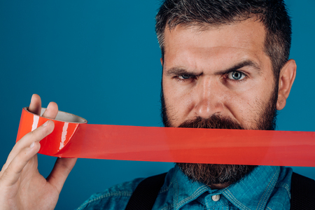 International Human Right day. censorship. Brutal bearded male. man wrapping mouth by adhesive tape. Mind control and propaganda. Concept freedom of speech and press. hidden aggression.
