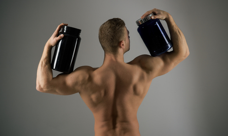 Eat a healthy diet. Strong man hold supplement bottles. Muscular man with vitamin supplements. Bodybuilding sport and fitness. Vitamin diet and sport nutrition. Keeping your energy level up Stock Photo