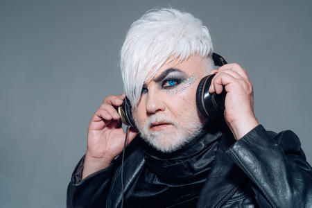 Music chose me. Transgender person listen to music. Bearded man with male makeup wear headphones. Hipster man with fashion hairstyle. Hipster fashion style. Male makeup look