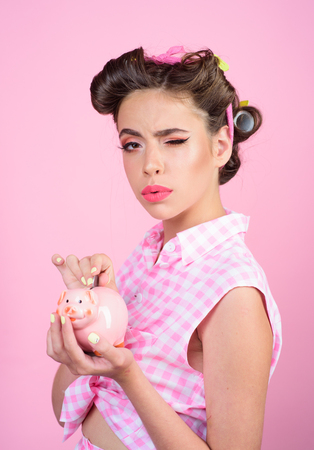 pinup girl with fashion hair. pretty girl in vintage style. pin up woman with trendy makeup. loan. Money. Housewife. retro woman with moneybox. So we got a deal.