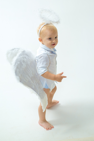 Enjoying magic moment. Little boy with angel wings and halo. Baby angel. Adorable little angel boy. Cute valentines cupid or cherub baby. Christmas angel. Christmas party celebration Archivio Fotografico - 113644605