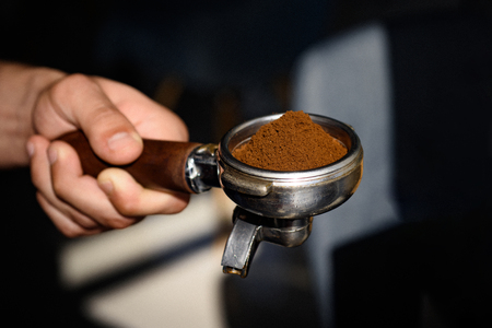 For true coffee connoisseurs. Coffee making in coffeehouse. Fresh ground coffee. Barista hold portafilter in hand. Barista brews espresso drink in cafe. Brewing coffee equipment