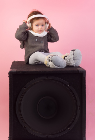 childhood and happiness. kid listen music with headset and mp3 on phone. small happy girl. audio speaker. little girl child smiling. winter kid fashion. having fun. Perfect song. She got great style Banque d'images - 113644686
