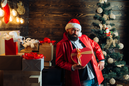 Bearded modern santa wishes Merry christmas and Happy new year. Christmas Celebration, holiday. Christmas tree background. Santa claus with red Christmas gift box.