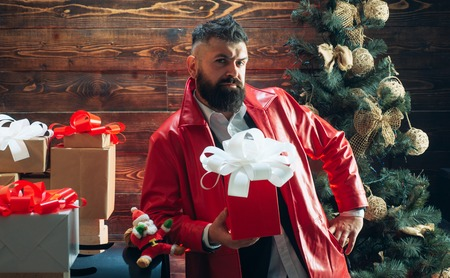 Santa claus with Christmas gifts. New year gift box. Bearded modern santa wishes Merry christmas and Happy new year. Stock Photo