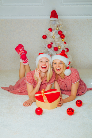 Christmas Best friends girl. White christmas tree red balls. Joyful friends celebrate christmas at home.
