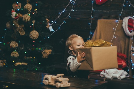 Winter kids. Kid enjoy the holiday. Christmas card. New year kids. Happy child with christmas gift box. Merry Christmas and Happy Holidays. Smiling child peeping from behind tree in living room.