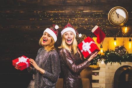 Beautiful Santa Clause woman. Sexy Santa Clause girl friends in elegant dress. Christmas gift. Santa woman posing. Sensual two girls for Christmas.