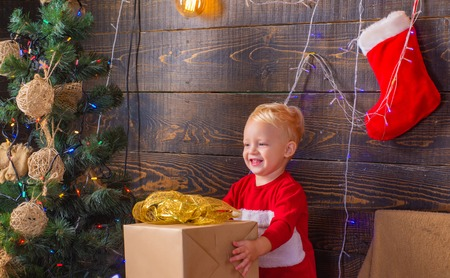 Christmas children. Cute little child near tree. Christmas kids. Smiling child peeping from behind Christmas tree in living room. Cute little child girl is decorating the Christmas tree indoors. 写真素材 - 113644953