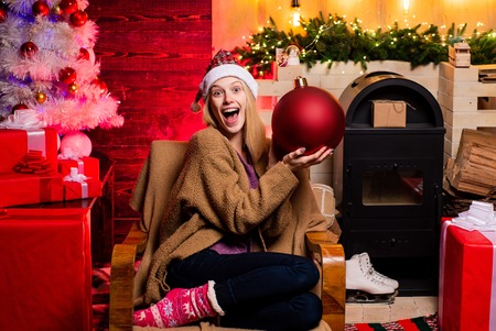 Funny Laughing Surprised Woman Portrait. Merry Christmas and Happy New Year. Bomb text copy space. Christmas Santa girl with bomb. Emotions. Banco de Imagens