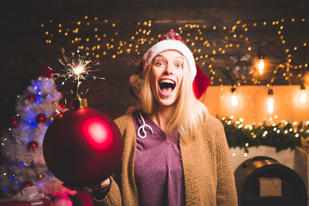 Christmas woman hold bomb. Creative boom. Bomb emotions. Fashion portrait of girl indoors with Christmas tree. Event. Christmas home atmosphere. Happy woman. Glamour celebration new year. Stock Photo