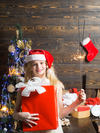 Opening gifts on Christmas and New Year. Merry Christmas and Happy New year. Teenager Christmas. Cute little girl is decorating the Christmas tree indoors Stok Fotoğraf