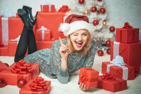 True Emotions. Young woman with Christmas present boxes in front of Christmas tree. New year eve girl. Beautiful Woman with Christmas box gif at Home. Christmas tree decorate at home. Stockfoto