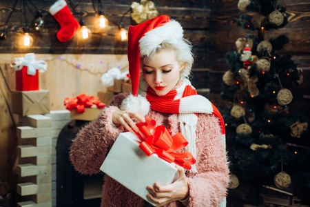 Crazy. Home Christmas atmosphere. Christmas happy. Young woman with christmas present boxes in front of christmas tree. Stock Photo