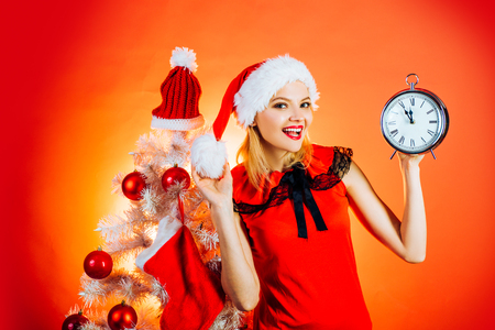Woman celebration Christmas on red background. New year party. New year clock - time christmas. Stock Photo