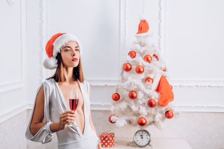 Christmas woman. We wish you a merry christmas. Pretty woman in red Santa Hat on holiday. Happy new year.