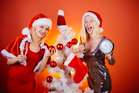 Smiling girls in santa clause costume. Christmas Best friends girl. Merry Christmas and Happy Holidays. Joyful friends celebrate christmas on red Background. Beautiful smiling woman.