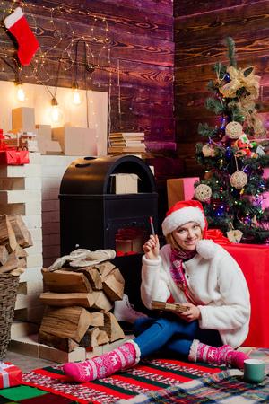 Christmas woman dress. Pretty girl wearing in Christmas dress. Beautiful Santa Clause woman. Sexy Santa Clause woman in elegant dress. Christmas gift. Santa woman posing. Banco de Imagens