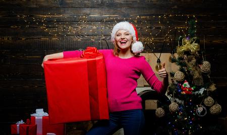 Christmas gift. Luxury girl celebrating New Year. Christmas fashion. Blonde Santa woman holding gift box at vintage wall. Sensual girl for Christmas. Seasonal Christmas holidays sale discounts.