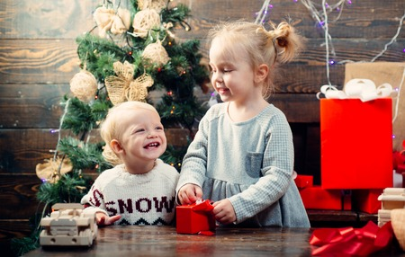 Happy children. Babies. Children gift. Christmas story concept. New year kids. Christmas kids. Happy small kids in santa hat with present have a christmas. Stok Fotoğraf