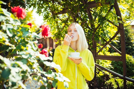 Young blonde woman drink coffee. Cafe or latte time. Stock Photo