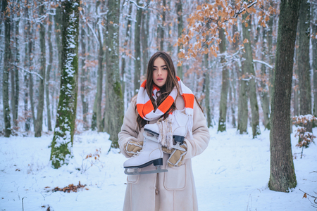 Winter portrait of young woman in the winter snowy scenery. Outdoor portrait of young pretty beautiful woman in cold sunny winter weather in park. Banco de Imagens