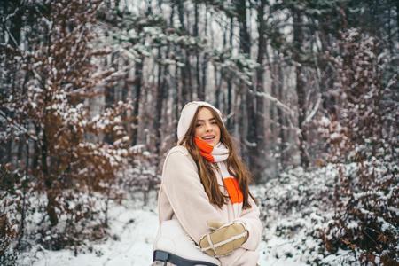 Sensual brunette winter girl posing and having fun. People in snow.