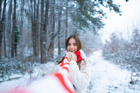 Outdoor portrait of young pretty beautiful woman in cold sunny winter weather in park.