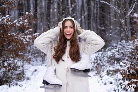 Laughing Girl Outdoors. Christmas girl outdoor portrait. Young woman winter portrait. Snowing winter beauty fashion concept. Winter woman. Banco de Imagens