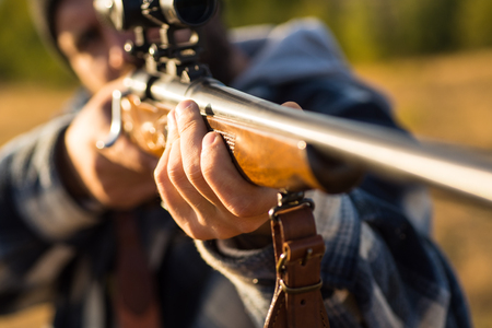 Hunter with shotgun gun on hunt. Barrel of a gun. Track down. Hunting Gear - Hunting Supplies and Equipment. Stock Photo