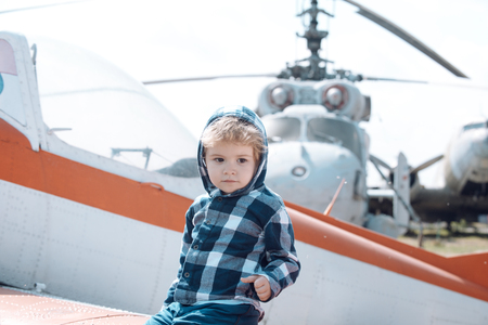 Its time to fly. Little kid have summer vacation. Cute boy child on vacation trip. Little child at helicopter field. Helicopter tour and travel. Air travel. Enjoying summer travel. Travelling by air. Stock Photo