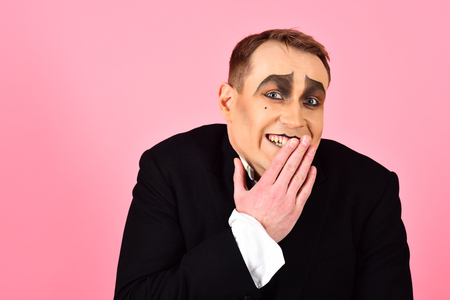 Laughing face. Comedian performer giggling. Mime artist. Mime with face paint. Man with mime makeup. Theatre actor miming. Stage actor miming. Theatrical performance art and pantomime. Comedy.