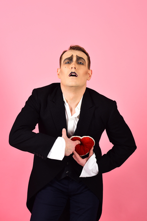 Pantomimine the feeling exactly like love. Mime actor has valentines celebration party. Love confession. Mime man celebrate valentines day. Comedian actor hold red heart. Happy valentines day. Stok Fotoğraf