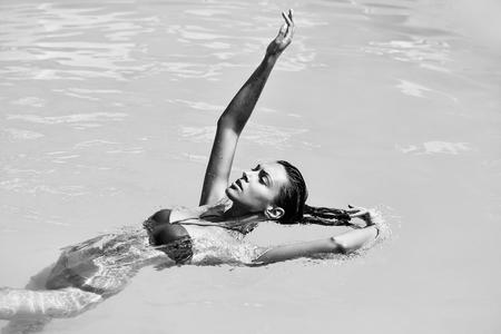 Model in pool raised hand Imagens