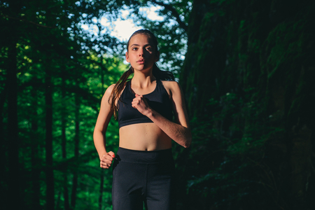 sporty woman training in green forest. Sport success. Fitness woman with good athlete body.