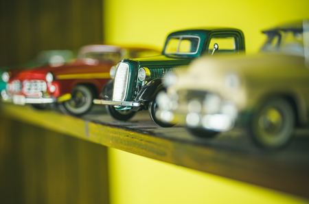 They look like real cars. Classic model vehicles or toy vehicles. Miniature collection of automobiles. Retro car models on shelf. Retro styled cars. Toy cars with retro design.