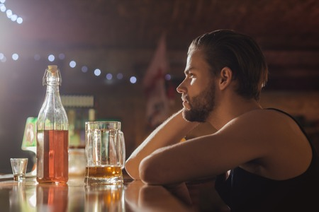 Man drinker in pub. Alcohol addict with beer mug. Handsome man drink beer at bar counter. Alcohol addiction and bad habit. Addicting to alcoholic drink.