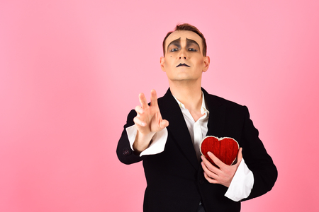 Passionate and poetic. Mime man hold red heart for valentines day. Mime actor with love symbol. Love confession on valentines day. Theatre actor pantomime falling in love, copy space.
