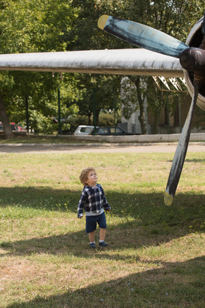 The world is yours to explore. Small child at plane field. Cute boy child on vacation trip. Small kid on summer vacation. Airplane tour and travel. Enjoying summer travel. Travelling by air. Stock Photo