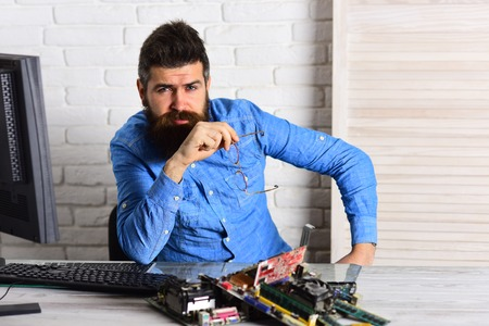 Confident in his skills. Engineer or technician at work. Bearded hipster works on fixing digital hardware. Bearded man repair circuit board. Assemblying of electronic devices. Computer and automation.