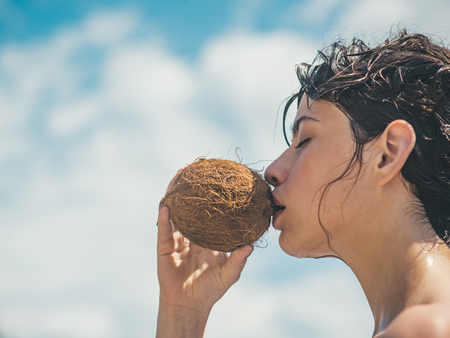 coconut oil production. coco milk. Clean eating diet, vegetarian and vegan. Woman is moisturizing her skin with a coconut cream. drinking beach cocktail. woman drinking coconut juice. summer vacation.