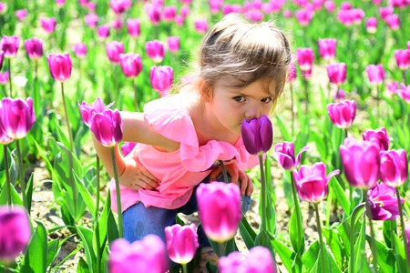 Pleasant time spending. Little girl in sunny spring. Small child. Natural beauty. Childrens day. Summer girl fashion. Happy childhood. Springtime tulips. face and skincare. allergy to flowers. Foto de archivo - 114534807