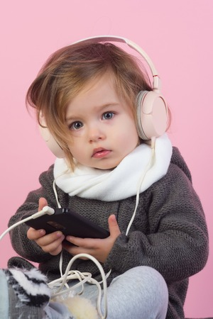 kid listen music with headset and mp3 on phone. having fun. winter kid fashion. small happy girl. little girl child smiling. childhood and happiness. Stock Photo