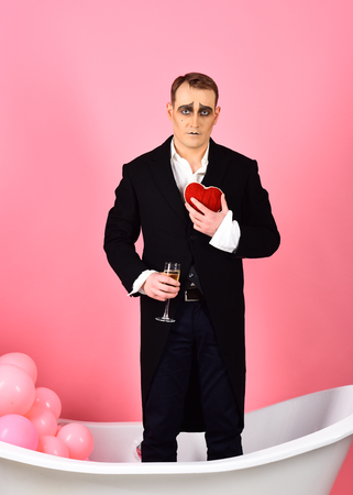 Comedian actor hold red heart and wine glass. Foto de archivo - 118696569